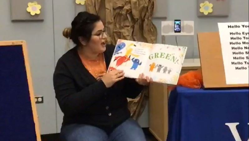 Woman reads aloud from picture book