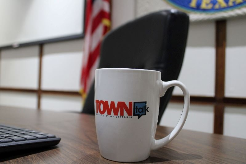 A coffee cup with the TOWNtalk podcast logo sits at the judge's bench at Municipal Court.