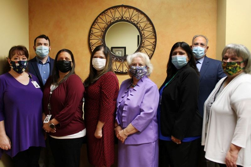 Finance employees wearing facial coverings pose for a group photo in the Finance lobby.