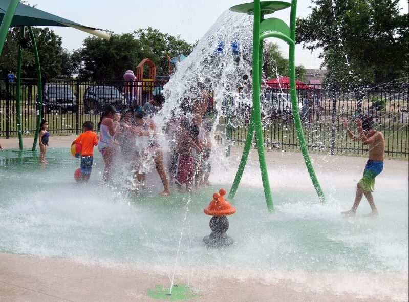 Young kids stand under a water pouring feature at a splash pad