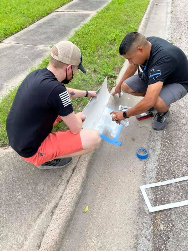 Two people squat near curb and use spray paint and stencils to paint address numbers