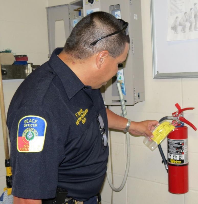 Fire fighter inspecting a fire extinguisher