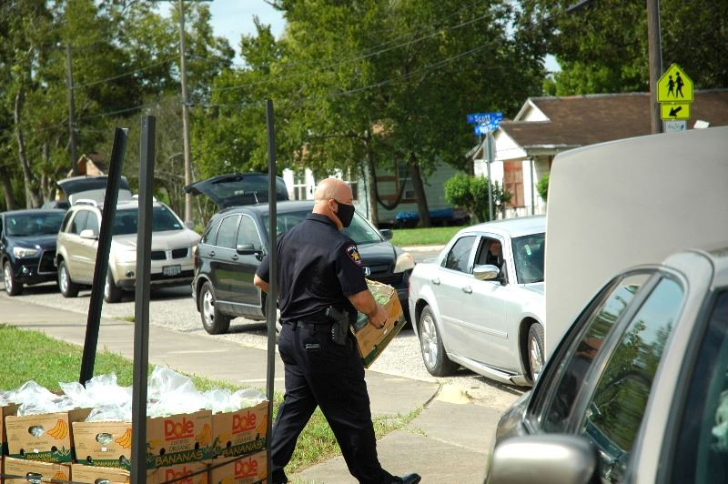 Man in police uniform carries food to line of vehicles
